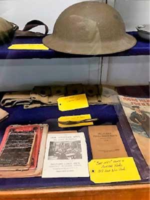 WWI exhibit: helmet, canvas belt, large bayonet.